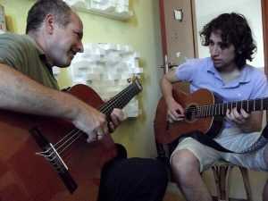 אוריאל אטלס מנגן על גיטרה עם תלמיד